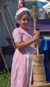 Elizabeth, daughter of Duchess Ilish, teaches butter churning.