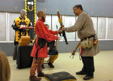 Master Urho received the ceremonial quiver of office from the outgoing champion, Lord Magnus.