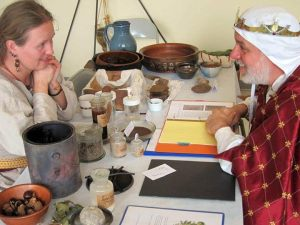 His Highness discusses the finer points of soap-making with Elskja Fjarfell, Aethlemearc's new A&S Champion. Photo by Hrolfr Fjarfell.
